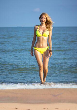 Portrait of gorgeous girl model on the beach on seaside wearing yellow swimsuit Banco de Imagens