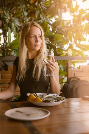 Beautiful girl close-up sits in a cafe at a table. On the table is a dish with oysters on ice and lemon. Holds a glass of white wine