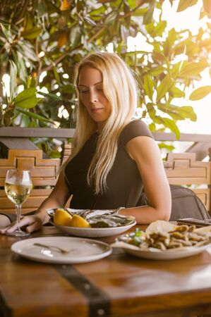 Beautiful girl close-up sits in a cafe at a table. On the table is a dish with oysters on ice and lemon Banco de Imagens