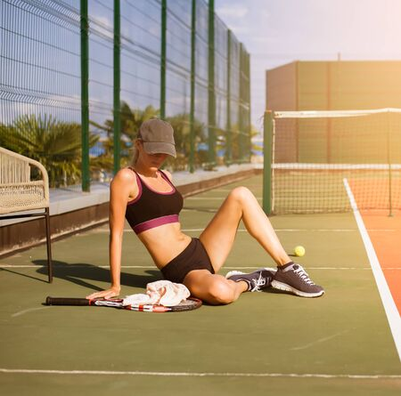 Slim young girl athlete tennis player is on the open tennis court in summer. Sits on the floor