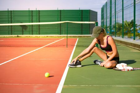 Slim young girl athlete tennis player is on the open tennis court in summer. Sits and touches the sore spot stretching on the foot Stock Photo