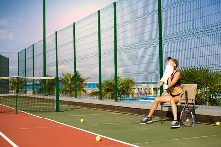 Slim young girl athlete tennis player is on the open tennis court in summer. Wipes up sweat with a towel after a game and sits on a chair. Stock Photo