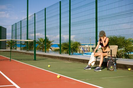 Slim young girl athlete tennis player is on the open tennis court in summer. Tired and sitting on the chair after the game