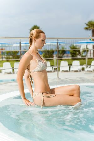 Beautiful young woman sitting on the side of a outdoor hot tub at the resort. Wearing a bikini Standard-Bild