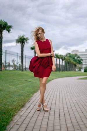 Beautiful young woman blonde with long hair in a fashionable burgundy dress Standard-Bild - 124871186