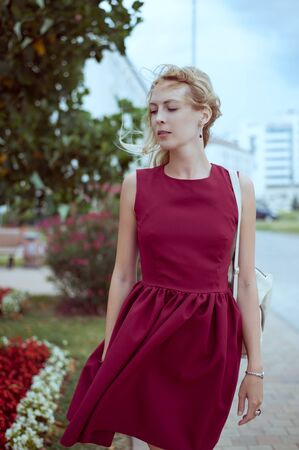 A beautiful young woman blonde with long hair in a fashionable burgundy dress stands on the street of a European city with developing hair Standard-Bild - 124871191