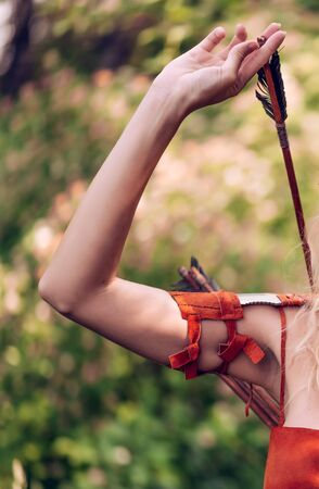 Close-up macro shot of a womans hand pulling an arrow for a bow from a quiver