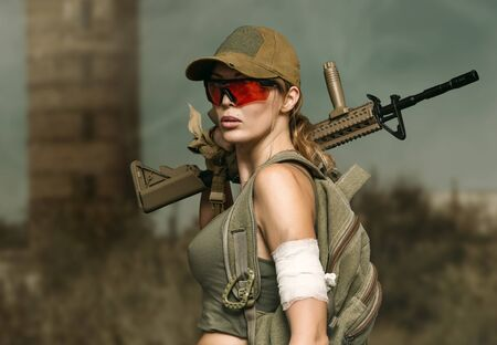 Dangerous military girl holding automatic rifle. Dooms day or war outddor 스톡 콘텐츠