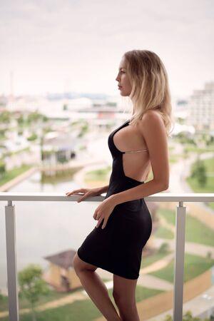 Junges schönes blondes Modefrauenmodell, das schwarzes Kleid mit offenem Rücken trägt