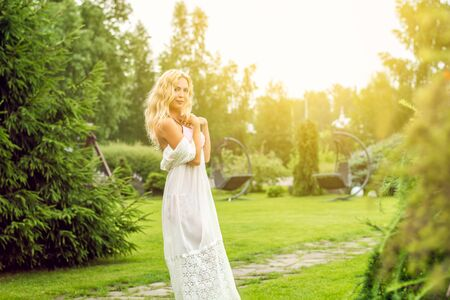 Youmg beautiful blond woman in beautiful summer garden stay barefoot on lawn