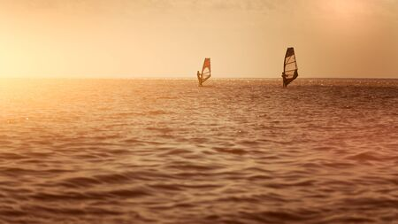Romance in the sea couple man and woman together sailing on a windsurfing board while on vacation in the south