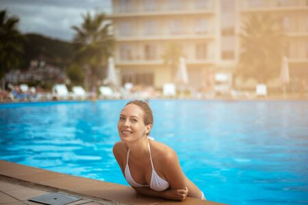 Beautiful happy girl with a smile in a hotel pool in a southern tropical resort wearing white bikini swimsuit
