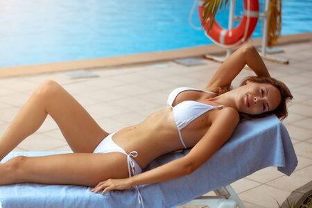 A beautiful girl with a perfect slim figure in a white bikini swimsuit is relaxing on a sunbed by hotels pool in the resort 版權商用圖片
