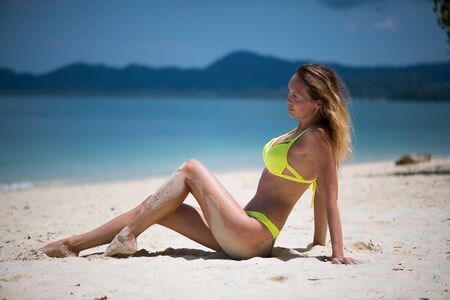 Young slim beautiful girl sits and relaxes near the sea or ocean waves in yellow swimsuit on a sandy beach on tropical resort
