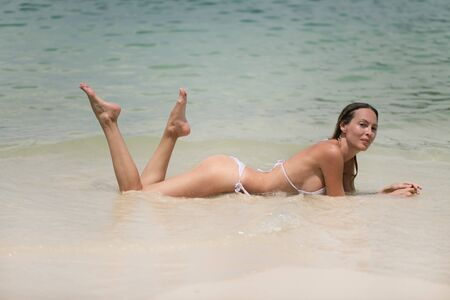 Young slim beautiful girl with wet hair relaxes in the sea or ocean waves in white bikini swimsuit on a sandy beach, tropical resort 版權商用圖片