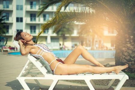 A beautiful woman with a perfect slim figure in a white bikini swimsuit is relaxing on a sunbed by hotels pool in the resort 版權商用圖片