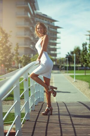 Beautiful young woman in a blonde in a sexy trendy white summer dress and sandals stay in a park bridge