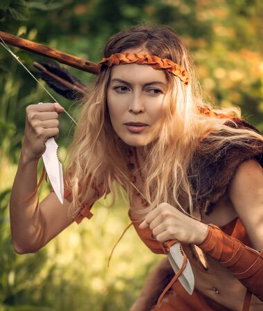 Beautiful girl archer with long blond hair with a bow and arrowson a back holding two steel knifes cold arms