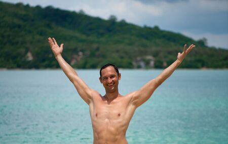 Portrait of a handsome happy man at tropical resort with teeth smile and raised his arms up and spread them apart 版權商用圖片
