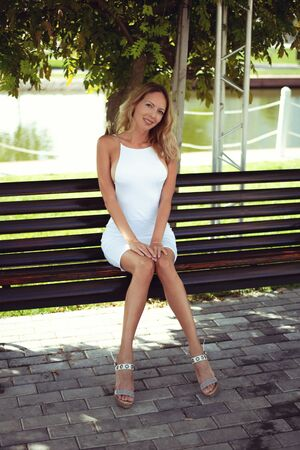 Beautiful young woman in a blonde in a trendy white summer dress and sandals sits on a park bench