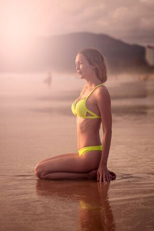 Portrait of Young happy beautiful girl relaxes on the sea or ocean sandy beach in yellow swimsuit on tropical resort