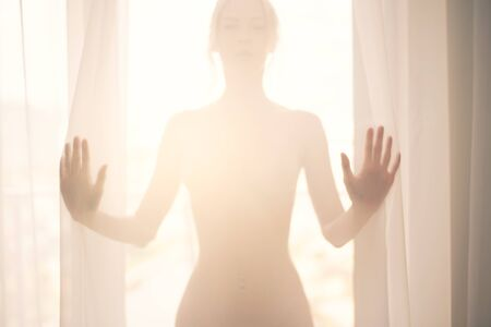 Defocus. High key light silhouette of a beautiful slender woman on the background of window behind a transparent curtain