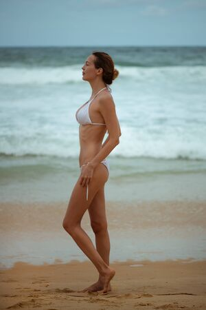 Young slim beautiful woman in sunglasses near the sea or ocean waves in white bikini swimsuit on a sandy beach, tropical resort