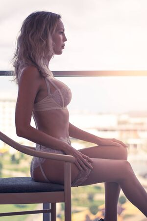 Beautiful sexy woman in elegant stylish expensive lace underwear on the balcony of her apartment 版權商用圖片
