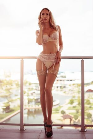 Beautiful sexy woman in elegant stylish expensive lace underwear posing on the balcony of her apartment