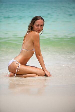 Young slim beautiful girl with wet hair sits and relaxes in the sea or ocean waves in white bikini swimsuit on a sandy beach, tropical resort 版權商用圖片
