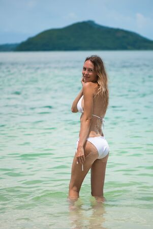 Young slim beautiful girl with wet hair stay in the sea or ocean waves in white bikini swimsuit on a sandy beach, tropical resort