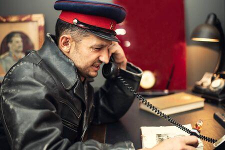 L'officier de sécurité soviétique, un employé de la Commission extraordinaire panrusse de lutte contre la contre-révolution et le sabotage, porte une casquette avec une étoile rouge et un marteau et une faucille, est assis à une table dans son bureau Banque d'images