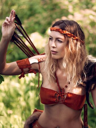 Beautiful girl archer with long blond hair with a bow and arrows dressed in leather and wrist wear pulls an arrow out of the quiver Reklamní fotografie