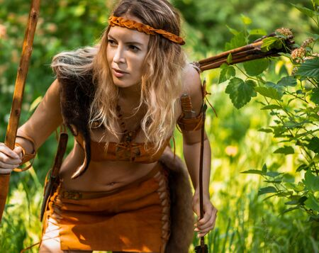 Beautiful girl archer with long blond hair with a bow and arrows dressed in leather and wrist wear