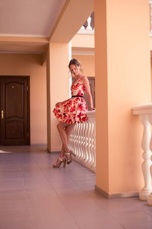 Beautiful young woman model demonstrates a short cocktail summer dress with a full skirt in a red and white flower with a belt
