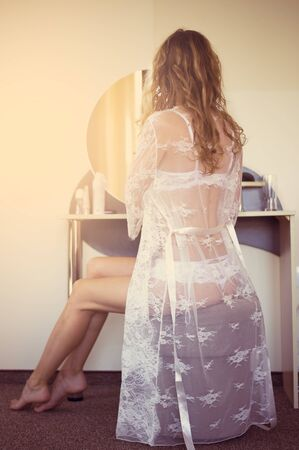 Beautiful young woman in white lace peignoir sits in front of a mirror in a boudoir in the bedroom