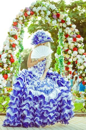 Costume stylization of a beautiful woman under a medieval or fairy princess, queen or aristocrat. Chic hat with feathers, an old dress, a wig with curls