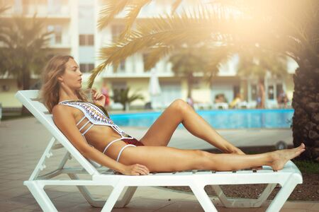 A beautiful woman with a perfect slim figure in a white bikini swimsuit is relaxing on a sunbed by hotels pool in the resort
