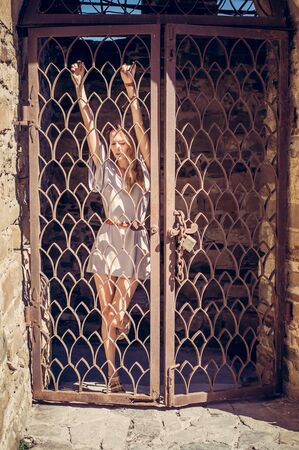 Beautiful stylish girl in a fashionable summer dress posing at the old grill gate in the fortress