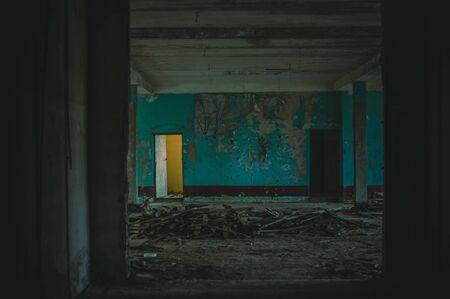 Defocus horror halloween background. Dark room in an abandoned ruined building. Light from the door