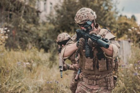 Two men in military camouflage vegetato uniforms with automatic assault rifles with optical sight aiming and shooting in the high grass in the forest
