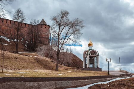 The red brick wall and the north tower of the ancient medieval fortress in Nizhny Novgorod Kremlin and Orthodox alarm bell