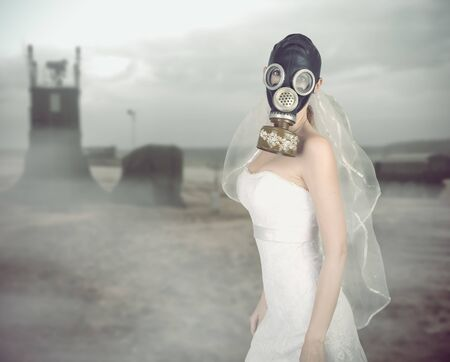 cyberpunk Bride in veil dress and protective mask in a gas mask with rhinestones style posing on a delicate background