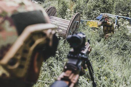 Military man aims from a rifle with an optical sight at another military man of the enemy in the forest.