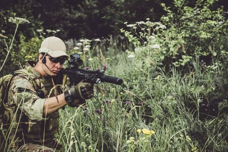 Focus on gun. A military man or airsoft player in a camouflage suit sits in the grass and aims from an automatic rifle with optical sight to the side