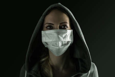 Young serious woman wearing medical protective face mask and hood in the night