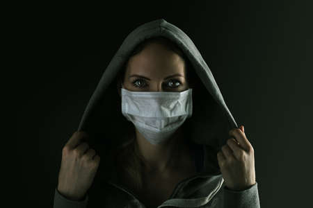Dark photo of Young serious woman wearing medical protactive face mask and hood in the night