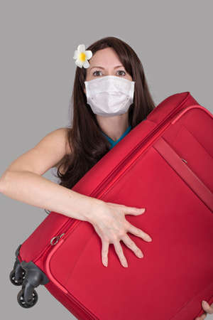 Frightened tourist woman in a medical mask holding a red suitcase Standard-Bild