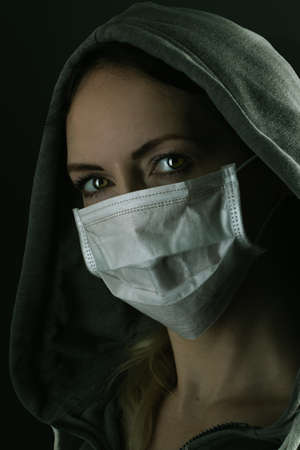 Young serious riot woman wearing medical protective face mask and hood in the night