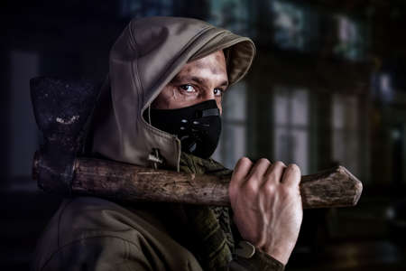 Young handsome man with ax wearing medical protective face mask and hood Standard-Bild